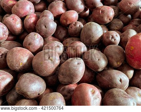 Large Pile Of Red Unpeeled Raw Potatoes Display At A Farmers Marketing
