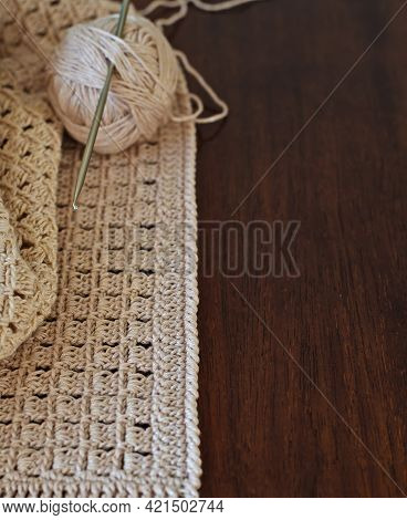 Handmade Crocheted With White Cotton Threads On A Wooden Table.