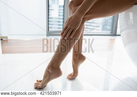 Hand, Ankle, Foot Of Woman Touching Smooth Hairless Leg Skin