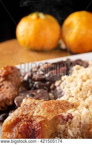 Brazilian Feijoada, White Dish With A Delicious Brazilian Feijoada, Rice, Farofa, And Fried Pork Wit