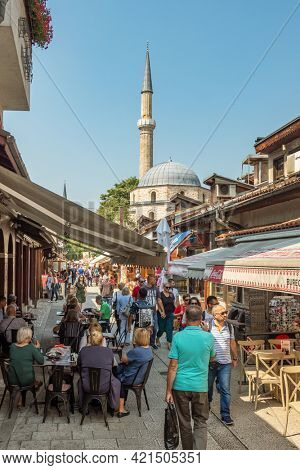 Sarajevo, Bosnia and Herzegovina - August 27, 2019: Street scene from Sarajevo, Bosnia and Herzegovina. Unidentified people walking and sitting in outdoor cafe with mosque at background at summer day