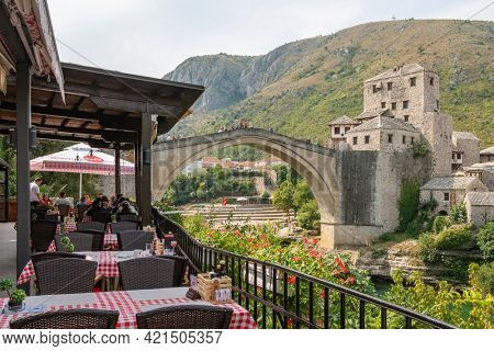 Mostar, Bosnia and Herzegovina - August 30, 2019: Outdoor restaurant with a view at Stari Most bridge in old town of Mostar, Bosnia and Herzegovina