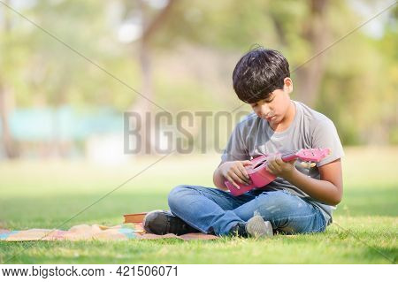 A Half-thai-indian Boy Relaxes By Learning To Play Ukulele Strings While Learning Outside Of School