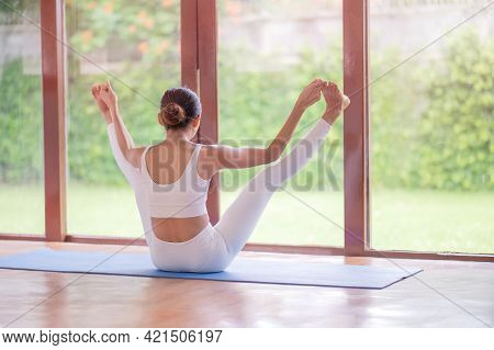 Asian Women Meditation And Stretching Relax Their Muscles By Doing Yoga In The Room