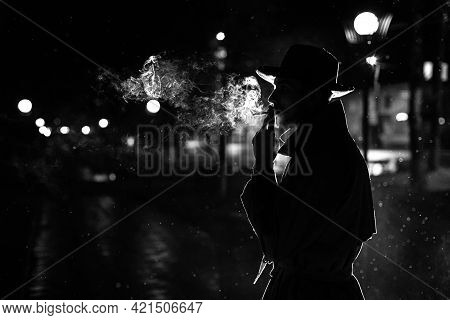 Dark Silhouette Of A Man In A Hat Smoking A Cigarette In The Rain On A Night Street