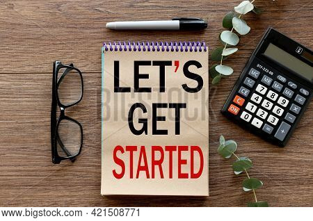 Let's Get Started. Lies On A Wooden Background, A Notebook With Craft Pages. Text On Notepad.
