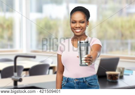 sustainability and people concept - portrait of african american woman in turquoise shirt with thermo cup or tumbler for hot drinks over home kitchen background