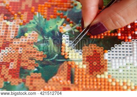Girl Using Tweezers Takes Incorrectly Glued Yellow Acrylic Rhinestones From The Diamond Picture 3d