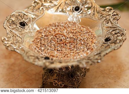 Wedding Rings Lie On A Dish With Wheat, A Tradition Among Newly Married Couples