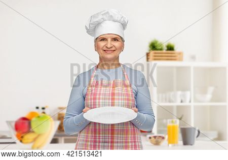 cooking, culinary and old people concept - portrait of smiling senior woman or chef in toque in apron holding empty plate over home kitchen background