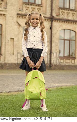 Happy Preschool Girl With Backpack In School Yard. Back To School. Child In Uniform Carry School Bag
