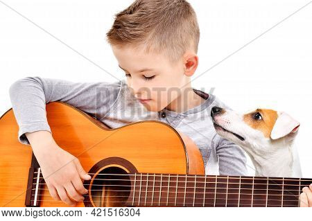 Portrait Of A Cute Boy Playing Acoustic Guitar With His Dog Jack Russell Terrier Isolated On White B