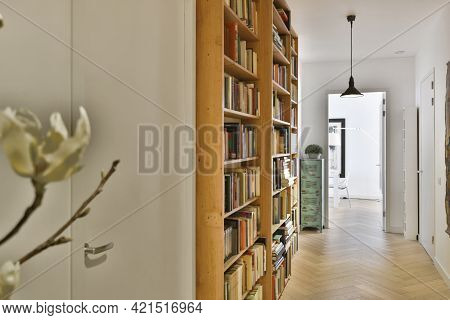 Perspective View Of White Apartment Corridor With Parquet Floor And Wooden Bookcases With Books Unde