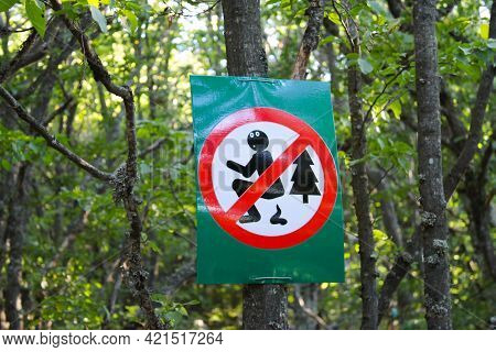A Sign On A Tree In A Forest Or Park Prohibits People From Pooping In Nature.