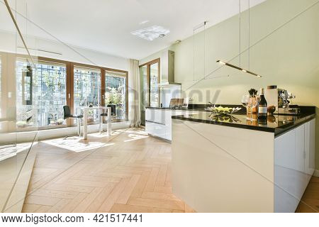 Big Panoramic Windows In Light Kitchen With White Cabinets And Black Counter Under Shiny Lamps