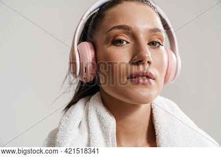 Young white woman with ponytail standing over white wall background, wearing wireless headphones and towel over her neck, close up