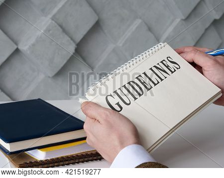 Manager Reads Guidelines And Holds Blue Pen.