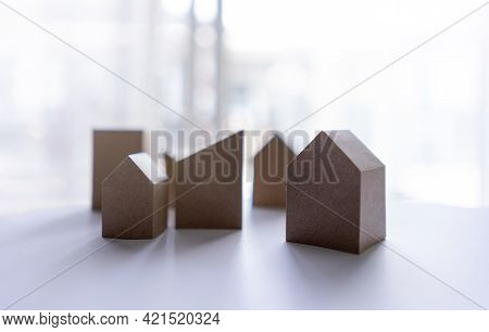 Many Small Miniature Houses On The Background Sunshine And Shadows. Buy House And Loan To Business H