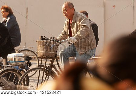 Shanghai, China, Asia - November 20, 2008: Old Man Riding A Bicycle In The Chaotic Traffic Of Shangh