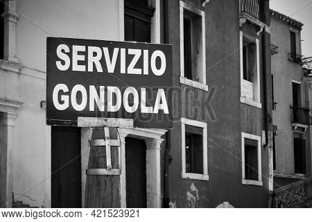 Gondola service sign by canal in Venice. Black and white photography