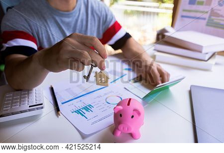 Close Up Young Man Showing House Key From Saving Money To Buy A New House. Loan Or Save Money For Bu