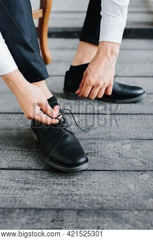 Young Man Puts On Black Shoes And Ties Laces, Close-up Of Male Hands. Selective Focus.