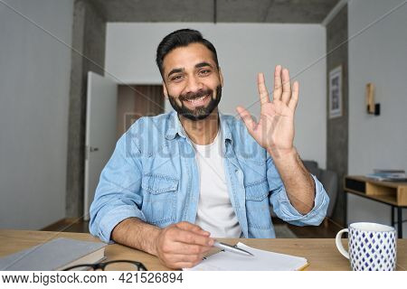 Young Happy Indian Hispanic Arab Teacher Talking On Video Conference Call Greeting Waving Hand Using
