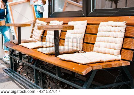 Outdoor Bench With White Soft Seat Cushions And Mounted Small Rounded Tables. Restaurant. Pillows. O