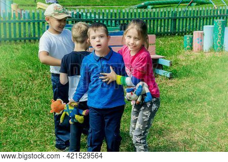 Omsk, Russia - June 16, 2019. Children Have Fun Playing With A Boy With Down Syndrome On A Walk In K
