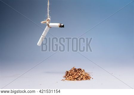World Tobacco Control Day. An Extinguished Cigarette Hangs Over A Pile Of Tobacco On A Blue Backgrou