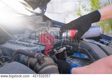 Cleaning The Car Battery Terminal From Dirt And Oxidation. Car Service, Repair Concept. Spraying Wit
