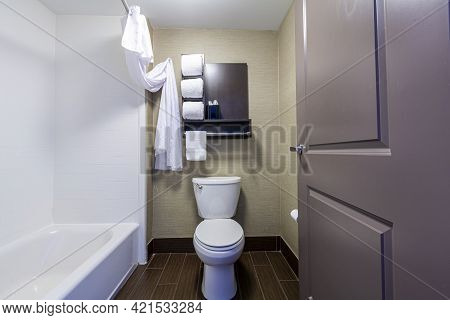 A Small Bathroom And Toilet In A Hotel With White Towels Folded And Placed On Shelves. A Bathtub Wit