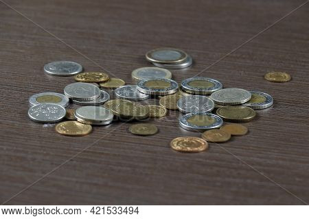 Silver And Bronze Metal Money Several International Currencies Pile On Wooden Background