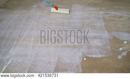 Priming The Concrete Floor With A Roller. Professional Floor Primer. Leveling Concrete Floors. Floor