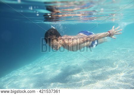 Child Boy Swimming Underwater In Mediterranean Adriatic Sea In Croatia