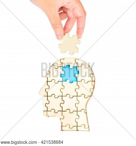 Female Hand Placing The Missing Brain Piece Of The Jigsaw Puzzle Forming A Human Head Isolated On Wh