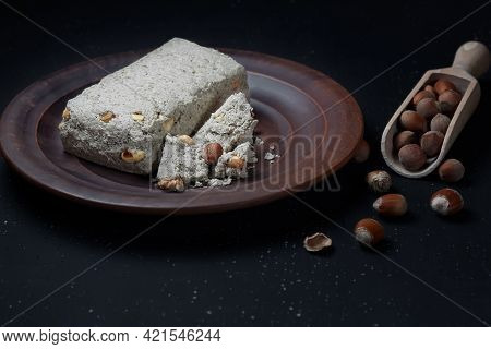 Whole Halva And Small Pieces Of Halva With Peanuts And Hazelnuts On A Clay Plate. Black Background.