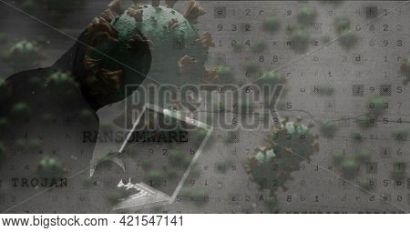 Composition of hooded hacker using laptop with covid cells and ransomware trojan messages on screen. global coronavirus pandemic and cyber security concept digitally generated image.