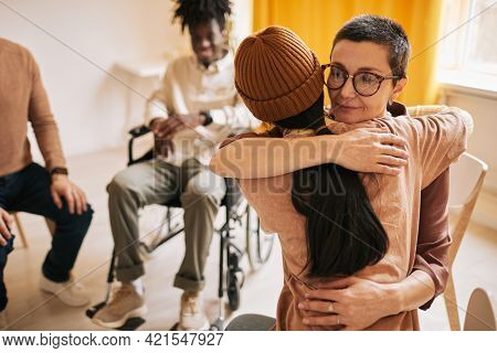 Portrait Of Female Psychologist Embracing Young Woman During Therapy Session In Support Group, Copy