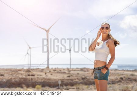 Young Woman Standing Near The Wind Generators
