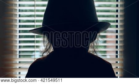 In The Background Is The Silhouette Of A Man In A Hat. There Are Blinds In The Background. Detective