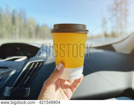 A Yellow Paper Cup With Any Hot Drink In The Hand Of A Woman Who Is Driving