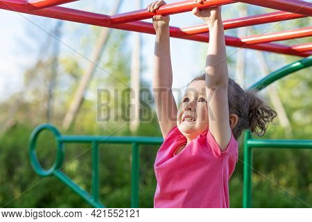 Child And Sport. Little Active Emotional Pensive Girl On Playground In Park, Hanging On Horizontal B