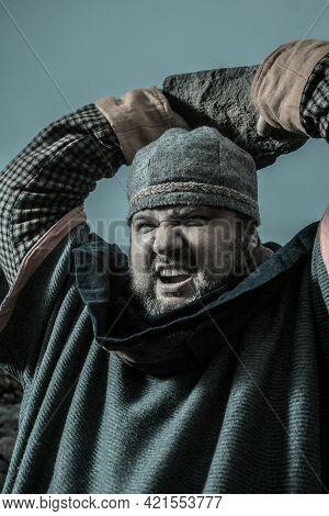 Brutal Scandinavian Warrior Throwing Big Boulder Outdoors