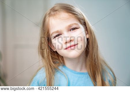 A Little Girl With Long Blond Hair Made A Make-up, Drew Arrows On The Eyelids.