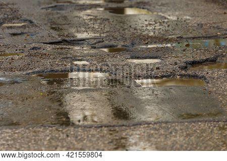 Potholes And Puddles On Bad Broken Wet Asphalt Road After Rain