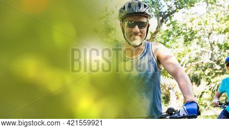 Composition of smiling fit caucasian man riding bicycle in forest with blur. sport, fitness and active lifestyle concept digitally generated image.