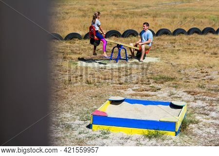 Defocus Girl Swinging On Swing On Playground With Young Man, Guy, Older Brother. Countryside. Bright