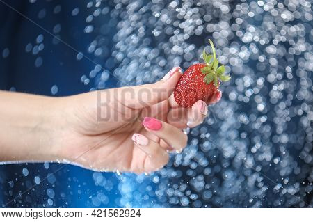 Woman Hand Close Up Holding Red Strawberry Under Drops Of Water. Girl Showing Red Strawberry On A Wa