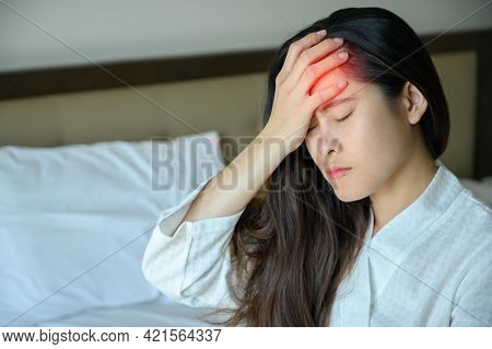 Portrait Of Young Asian Woman Sitting On Bed And Suffering From Headache. Headache Maybe Occurs From